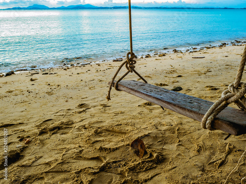 Fotografía  Wooden swing on the Beach beside the ocean in vacation time