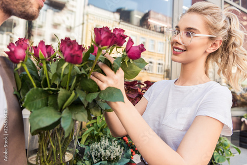 Cropped Image Of Smiling Florists Selecting Burgundy Roses