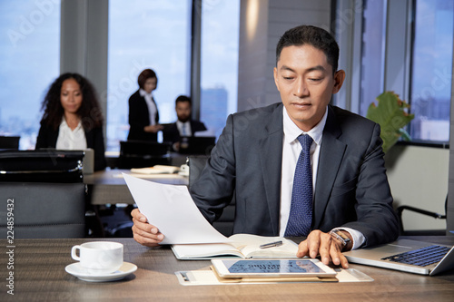 Adult Asian man with tablet and laptop sitting at table and reading papers in office with colleagues