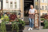 Fototapeta Fototapety na drzwi - smiling attractive florist standing on stairs of flower shop and leaning on open sign