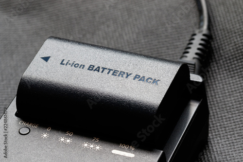 Obraz Rechargeable lithium-ion battery with charger - fototapety do salonu