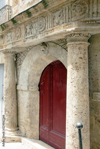Foto Ville de Pézenas, porche sculpté avec colonnades et porte rouge, département de