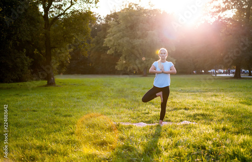 Tuinposter Ontspanning Yoga in the park, young woman doing tree pose vrksasana