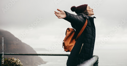 Woman happily breathing in the fresh sea air Canvas Print