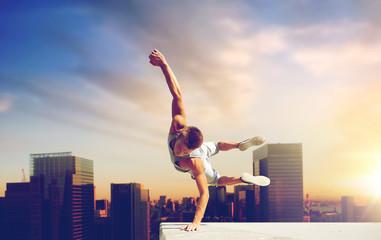 koncept ekstremnih sportova, parkura i ljudi - mladić skače visoko preko pozadine grada Tokya