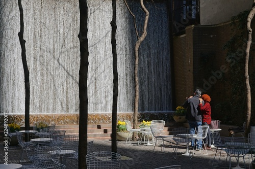 Fotografie, Obraz  Man and woman watching the waterfall in Paley Pocket Park, midtown Manhattan, New York City, amid yellow tulips and white tables and chairs