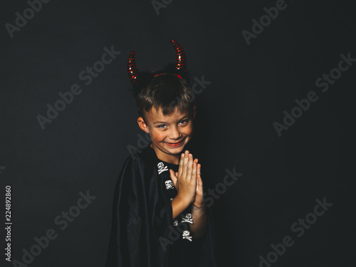 Fototapeta little boy with red halloween horns and black cape in front of black background