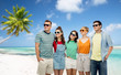 travel, summer holidays and tourism concept - group of happy smiling friends in sunglasses hugging over tropical beach background in french polynesia