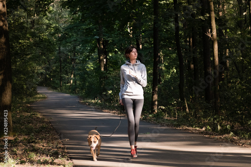 In de dag Jogging Woman jogging with dog in beautiful forest. Young female person with pet doing cross country running excercise in fresh air.