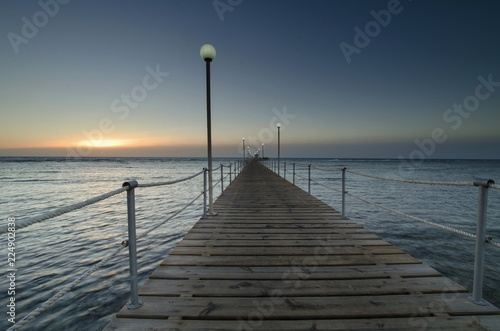 Sunrise over the sea and a light wooden pier.