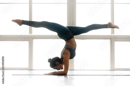 Photo Young yogi attractive woman practicing yoga, doing Pincha Mayurasana exercise, h