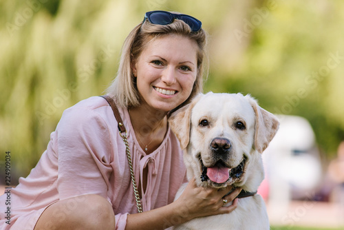 A beautiful blonde is sitting near her labrador retriever on the grass in the park Tableau sur Toile