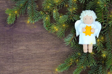 White Felt Christmas Angel With Yellow Star In Hands To Fresh Natural Branches Of Christmas Tree Spruce On Wooden Background