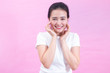 Portrait of happy young asian woman isolated on pink background. Beauty face with natural skin with hands touching face in v shape and smile.