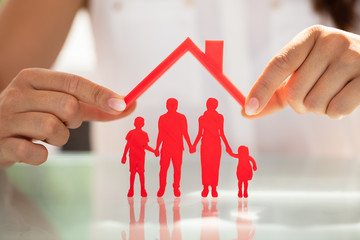 Obraz na Plexi Businesswoman Protecting Family Figures With Roof