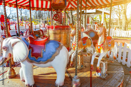 Poster Amusementspark Children outdoor colourful vintage Merry-Go-Round flying horse carousel in amusement holliday park in city. Attraction detail horses and animals with lots gold paintwork on traditional retro carnival