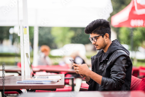 Fototapeta Young indian office worker using his phone in a street cafe obraz na płótnie