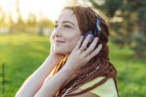 Photo Beautiful modern girl with dreadlocks listening to music with headphones in autumn Sunny Park