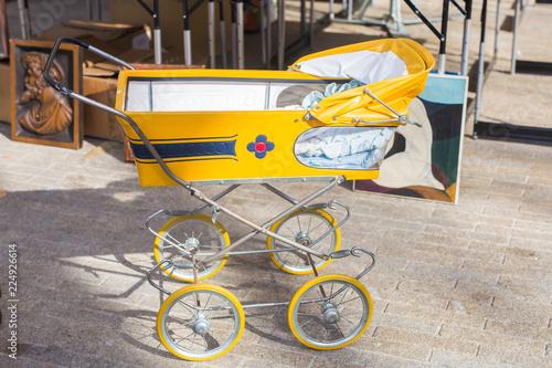 Foto  Vintage baby buggy or stroller, outdoors on flea market