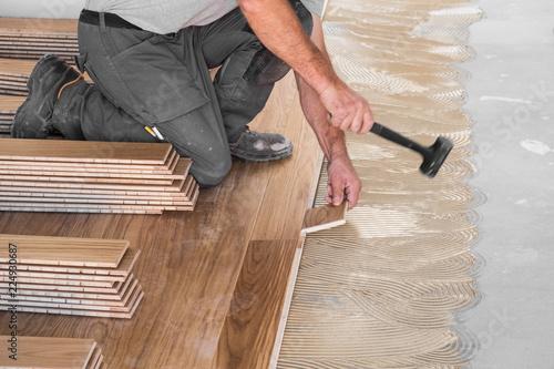 Fototapeta Worker installing wooden flooring boards on applied adhesive obraz na płótnie