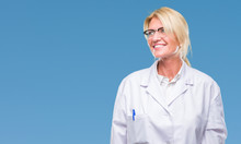 Middle Age Blonde Therapist Woman Wearing White Coat Over Isolated Background Looking Away To Side With Smile On Face, Natural Expression. Laughing Confident.