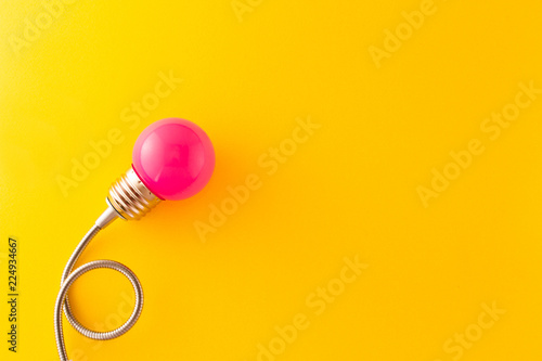 Foto  One pink decorative lamp on a bright yellow background.