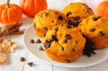 Autumn Pumpkin Chocolate Chip Muffins. Close Up Table Scene On A Bright White Wood Background.