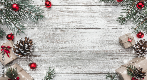 Christmas theme with fir branches, cones, globes, red bows, present boxes on white wooden background viewed from above, in snow, greeting card with space for text