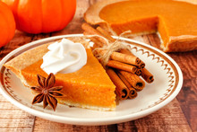 Slice Of Pumpkin Pie With Whipped Cream. Close Up Scene On A Rustic Wood Background.