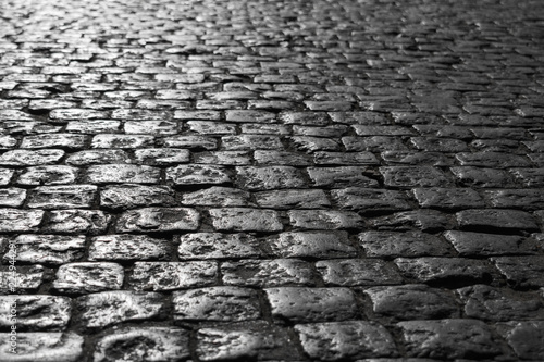 In de dag Stenen Black and white picture of a close-up of an old road with a texture of stone sun-drenched at sunset