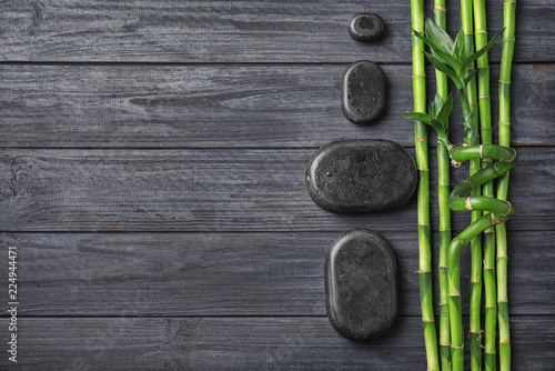 Bamboo branches and spa stones on wooden background, top view. Space for text