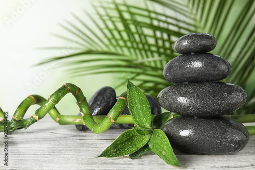 Spa stones and bamboo branches on wooden table. Space for text
