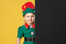 Little Girl In A Christmas Elf Costume On A Yellow Background. A Child Is Standing Next To A Place For Text, Copy Space. Blank Black Background.