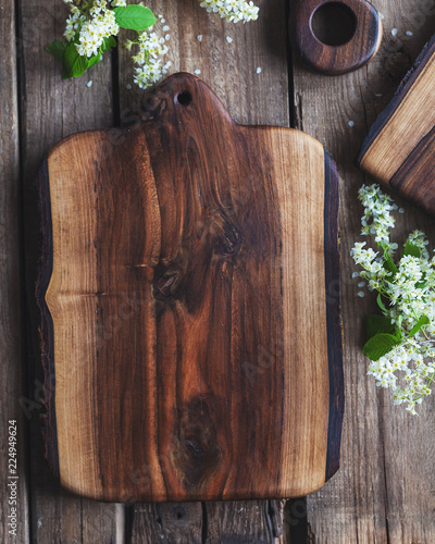 Handmade Walnut cutting Board on rustic wooden table with bark on 2 sides