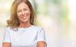 Middle age senior hispanic woman over isolated background happy face smiling with crossed arms looking at the camera. Positive person.