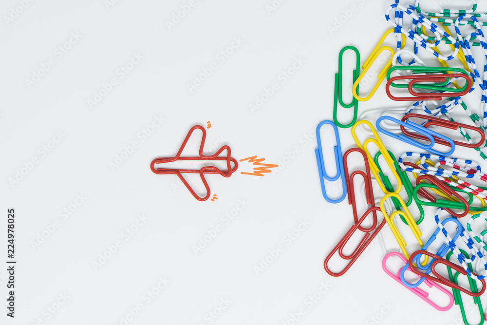 Fototapeta Business concept for group of stacked paperclip with another one red plane paperclip is point to another direction as a team leadership