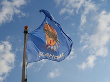 The Flag Of Oklahoma State Fluttering Up Above Clear Blue Skies From A Pole