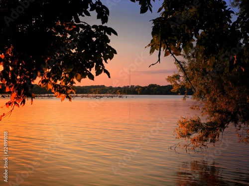 Sunset colors reflected in the waters of the lake at twilight Wallpaper Mural
