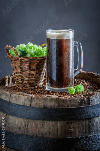 Tuinposter Bier / Cider Fresh pint of dark beer on old barrel