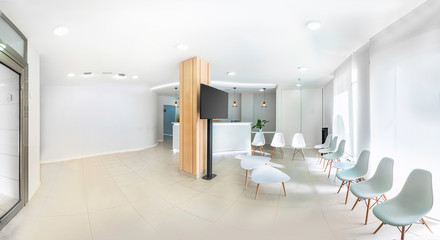 Panorama of a bright reception and waiting room in a clinic with desk, modern chairs and plants. Indoor mockup with screen with copy space.