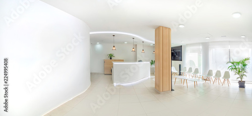 Fotografie, Obraz Panorama of a bright reception and waiting room in a clinic with desk, modern chairs and plants