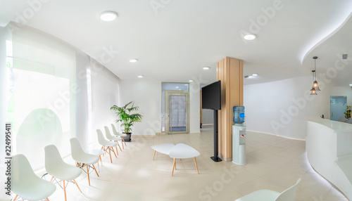 Cuadros en Lienzo  Panorama of a bright reception and waiting room in a clinic with desk, modern chairs and plants