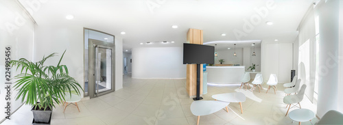 Fotografía  Panorama of a bright reception and waiting room in a clinic with desk, modern chairs and plants