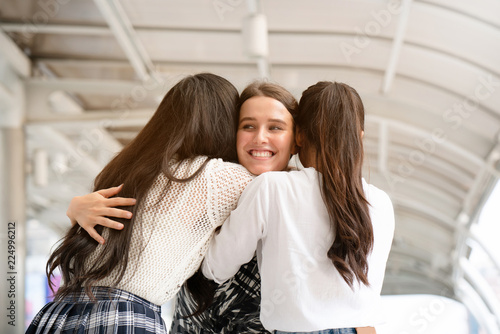 Fototapeta  Portrait of three women standing embracing each other with love caring