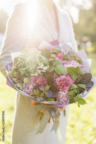 Young girl holding a beautiful spring bouquet. flower arrangement with hydrangea and garden roses. Color violet pink. Bright dawn or sunset sun
