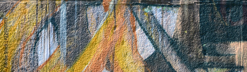 plakat Fragment of graffiti drawings. The old wall decorated with paint stains in the style of street art culture. Colored background texture in warm tones