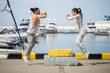 Caucasian fit couple in sportswear doing jumping squats on urban sea embankment with motor boats and yachts in summer day
