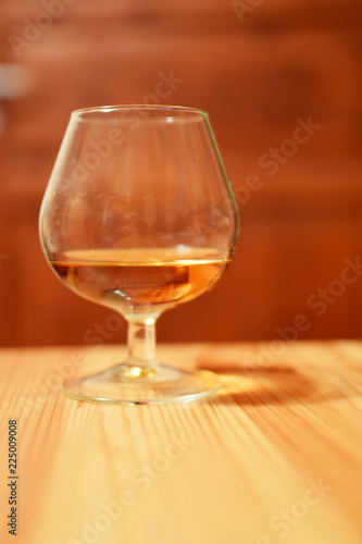 Fotobehang Alcohol One glass of brandy or cognac on wooden table on brown background.