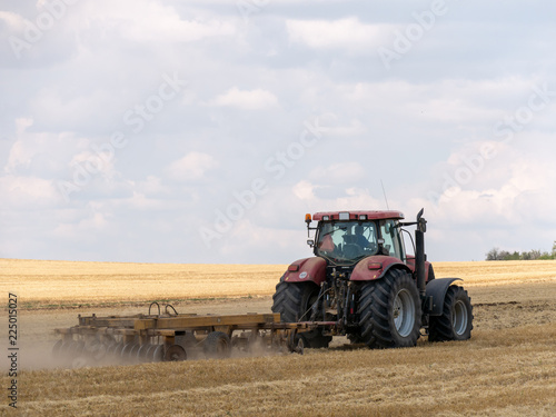 Red tractor with plow on harvest field. Summer field and red tractor. Tractor on harvest field. Lowing after harvest. Plowing on the field.