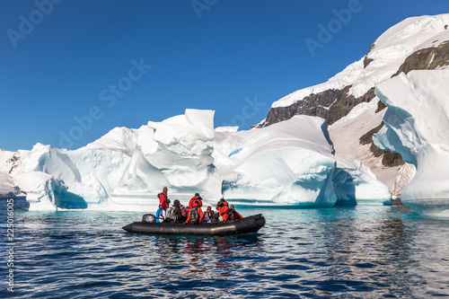Boat full of tourists explore huge icebergs drifting in the bay
